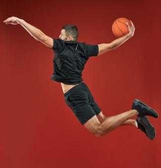 Knappe kaukasische bebaarde basketballer spelen in basketbal in sportcentrum