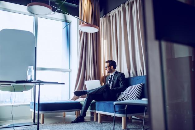 Knappe kaukasische bebaarde zakenman in pak en met bril zittend in kantoor op de bank, laptop op schoot houden, via raam kijken en glimlachen.