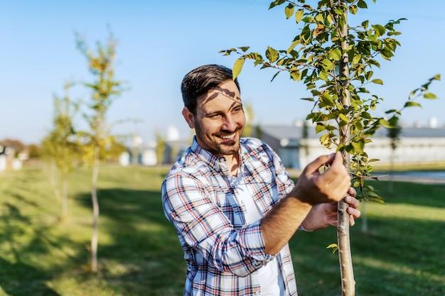Knappe kaukasische glimlachende landbouwer die zich in boomgaard bevindt en fruitboom controleert.