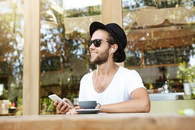 Knappe kaukasische hipster trendy hoed dragen en zonnebril die van vrije wifi genieten bij koffiewinkel