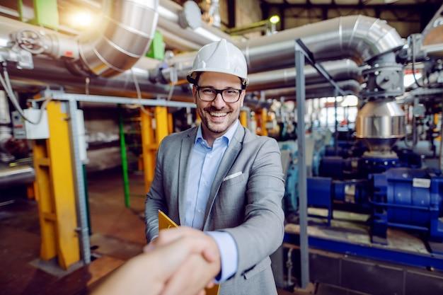 Knappe kaukasische manager in pak en met helm op hoofd houden map met documenten en handen schudden met investeerder terwijl je in de elektriciteitscentrale.