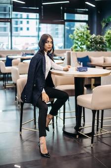 Knappe kaukasische vrouw in donkerblauwe blazer, zwarte broek en zwarte schoenen met lang donker golvend haar zit op een stoel in het café