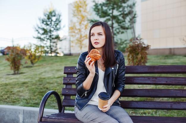 Knappe kaukasische vrouwenzitting in park en het eten van croissant