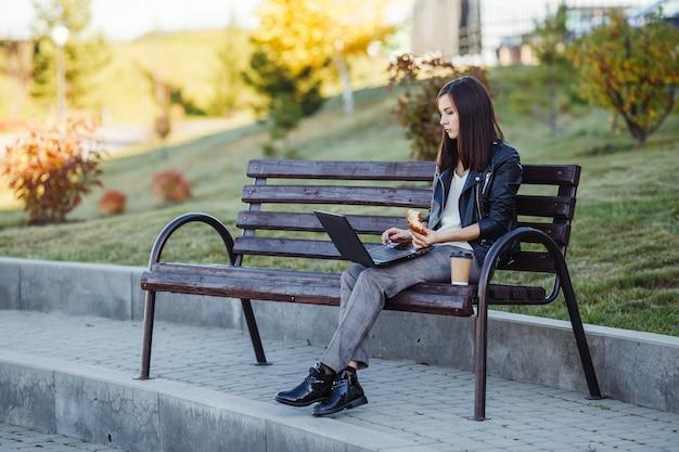 Knappe kaukasische vrouwenzitting in park met laptop en het eten van croissant met koffie