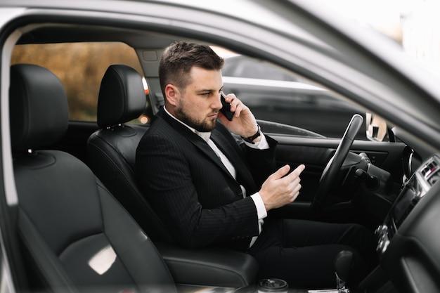 Knappe kaukasische zakenmanbestuurder binnen in voertuig met gadget en controlepost en het spreken met partners