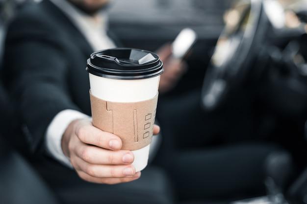 Knappe kaukasische zakenmanbestuurder binnen in voertuig met koffie en gadget en controlepost en het spreken met partners