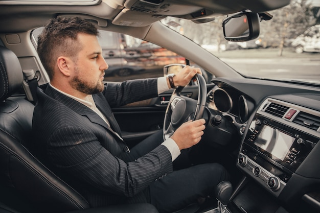 Knappe kaukasische zakenmanbestuurder binnen in voertuig