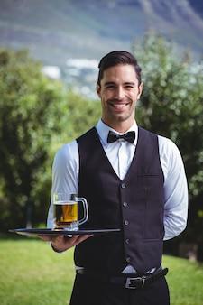 Knappe kelner die een dienblad met een pint bier houdt