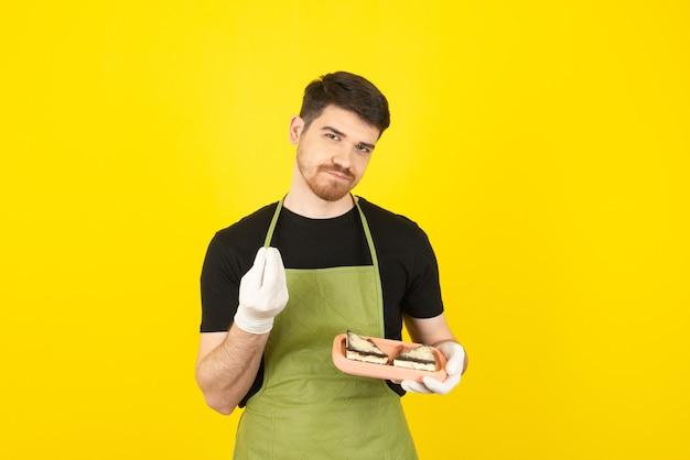 Knappe kerel die cakeplakken vasthoudt en smaakvol met de hand gebaren.
