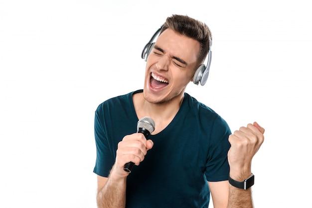 Knappe kerel die in hoofdtelefoons karaoke zingt.
