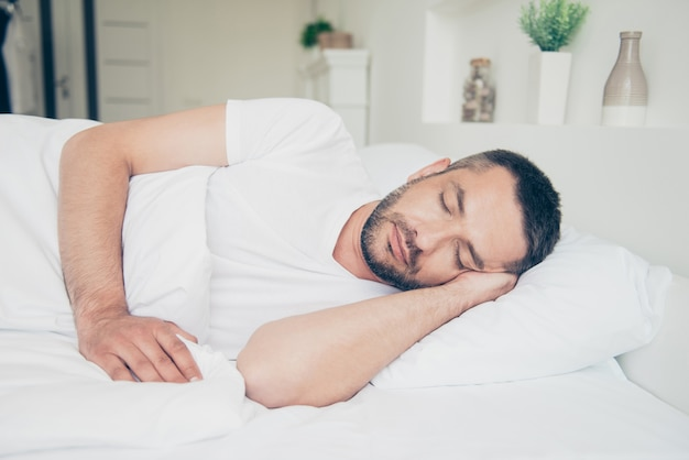 Knappe kerel die in zijn slaapkamer slaapt