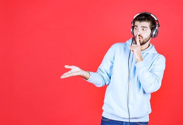 Knappe kerel die muziek luistert en stil gebaren maakt