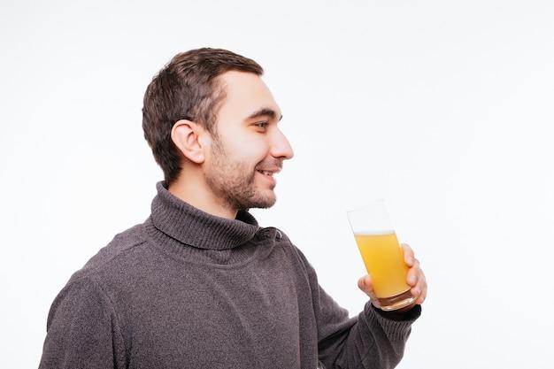 Knappe kerel drinkt sinaasappelsap op grijze muur