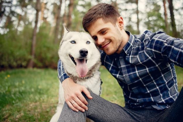 Knappe kerel in een de zomerpark met een hond