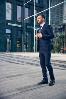 Knappe kerel in een mooi officieel pak dat in de buurt van een groot kantoor staat en denkt