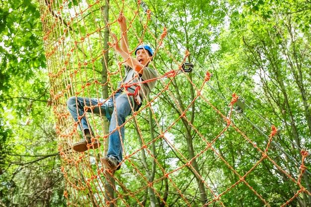 Knappe kerel in een park aan de touwen bereikt outdoors