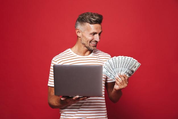 Knappe kerel in gestreept t-shirt glimlachend terwijl hij een fan van geld contant geld en een laptop vasthoudt die op rood wordt geïsoleerd?