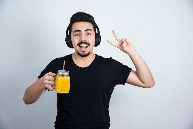 Knappe kerel in hoofdtelefoons met glaskop jus d'orange die overwinningsteken toont.