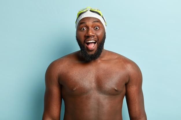 Knappe kerel met donkere huid en naakt lichaam, bereidt zich voor op zwemmen, draagt speciale hoed en bril, houdt mond wijd open