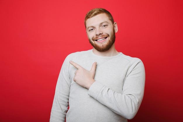 Knappe kerel met gemberbaard die en camera glimlacht bekijkt terwijl hij op heldere rode achtergrond staat en met wijsvinger opzij wijst