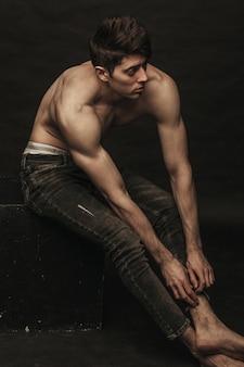 Knappe kerel met ontbloot bovenlichaam raakt zijn spijkerbroek aan.