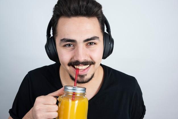 Knappe kerel model hoofdtelefoon drinken uit glazen beker met sinaasappelsap.