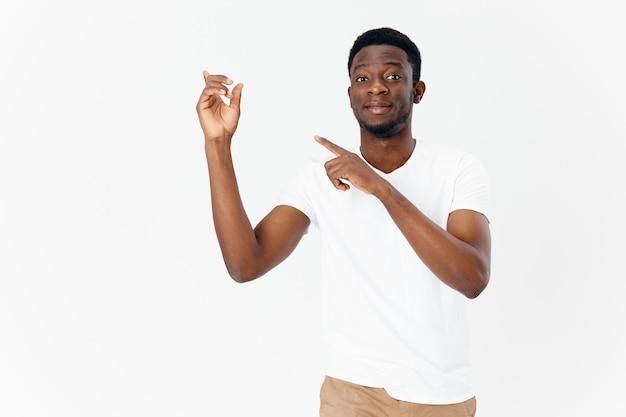 Knappe kerel van afrikaans uiterlijk toont een vinger opzij op een lichte muur en beige