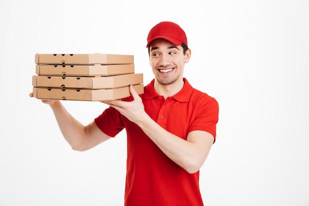 Knappe kerel van de leveringsdienst in rode t-shirt en glb-holdingsstapel pizzadozen, die over witte ruimte wordt geïsoleerd