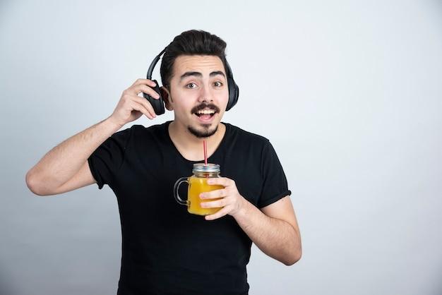 Knappe kerelmodel in hoofdtelefoons die glaskop met jus d'orange houden.