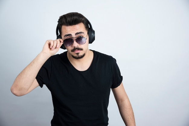 Knappe kerelmodel in hoofdtelefoons die met zonnebril tegen witte muur stellen.