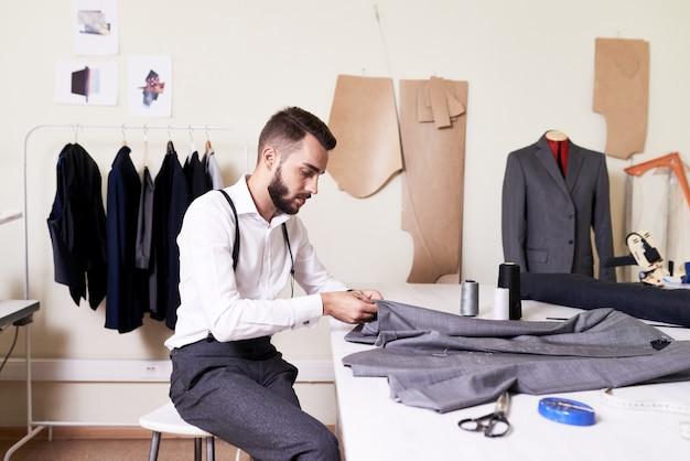 Knappe kleermaker werken in atelier