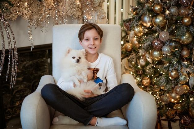 Knappe kleine blanke jongen op de bank met witte hond op een lichte kerstachtergrond merry chris...