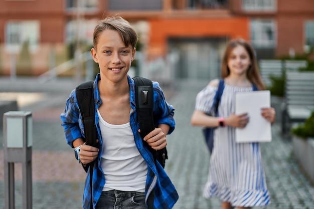 Knappe kleine jongen en mooi meisje dat naar school gaat met rugzak en boeken.
