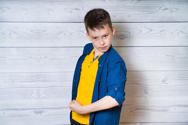 Knappe kleine jongen in jean kleding vertoont zijn spieren op een witte houten