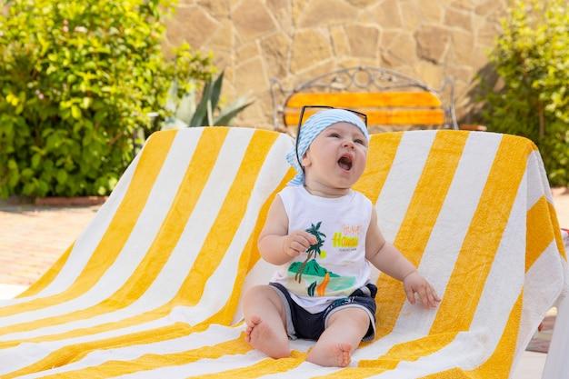 Knappe kleine jongen in zonnebril en een bandana zit op een ligstoel bij het zwembad. selectieve aandacht.