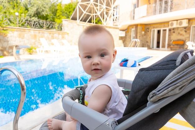 Knappe kleine jongen zit in een kinderwagen bij het zwembad. selectieve focus