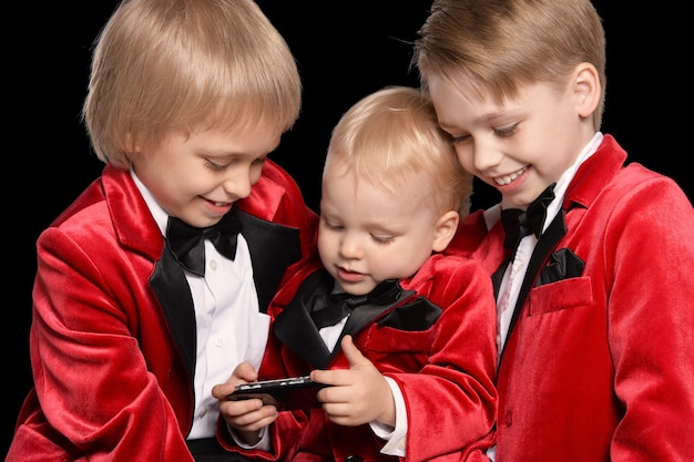 Knappe kleine jongens in een smoking met mobiel op zwarte achtergrond
