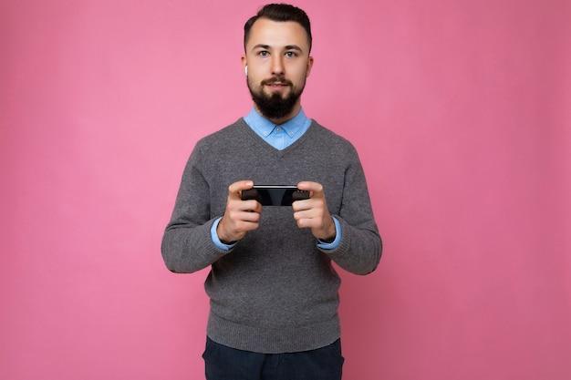 Knappe knappe brunet bebaarde jonge man met grijze trui en blauw shirt geïsoleerd op roze