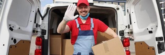 Knappe koerier haalt kartonnen doos uit busje en zwaait welkom