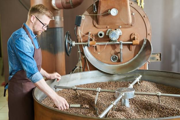 Knappe koffiebrander die zich door machine bevindt