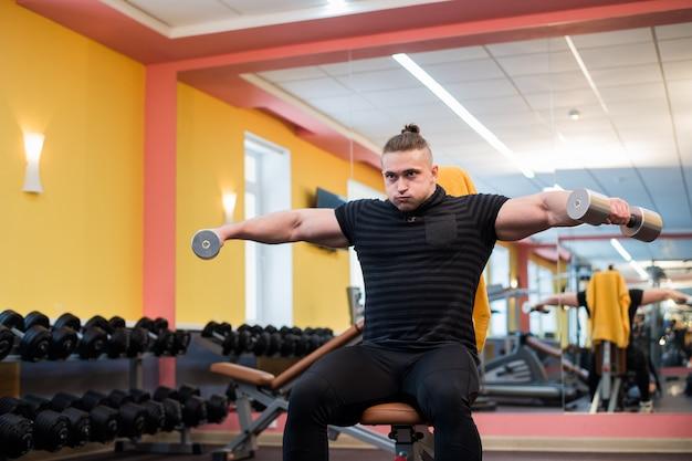 Knappe krachtige atletische man doen barbell schouderpers oefening. sterke bodybuilder met perfecte spieren.