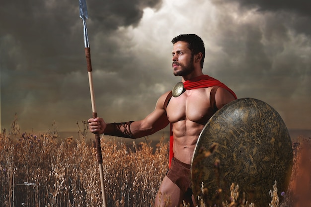 Knappe krijger met blote torso poserend tussen gras