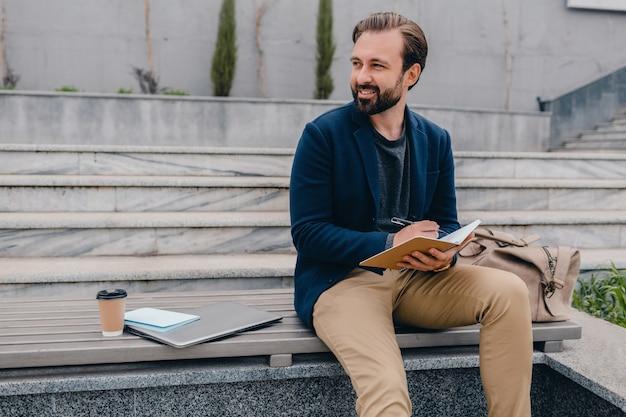 Knappe lachende bebaarde man aan het werk, schrijven in notitieboek