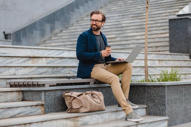 Knappe lachende bebaarde man in glazen die op laptop werkt