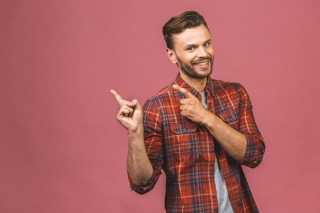 Knappe lachende bebaarde man weg te wijzen op roze achtergrond