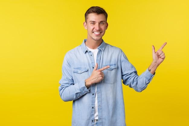 Knappe lachende gelukkige man met witte tanden, wijzende vingers naar rechts, klanten uitnodigen om reclame te bekijken, nieuw product demonstreren, speciale kortingsaanbiedingen, staande gele achtergrond