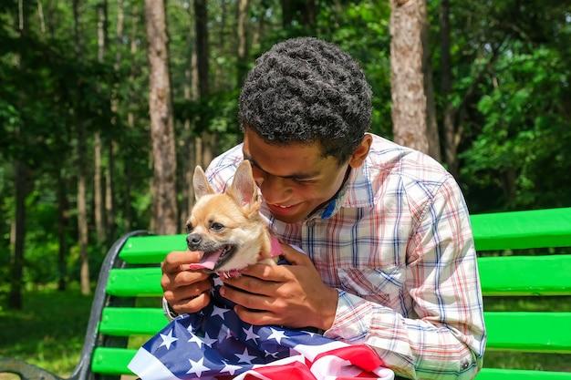 Knappe lachende jonge afro-amerikaanse man met een chihuahua-hond gewikkeld in de vlag van de v.s. buiten in de zomer