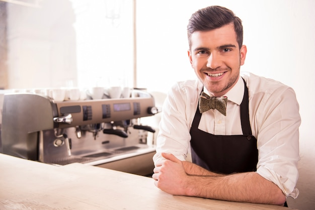Knappe lachende jonge barista in zijn café.