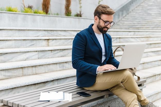 Knappe lachende jonge bebaarde man met jasje bezig met laptop zittend buiten op de stadsbank
