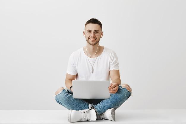 Knappe lachende jonge kerel met een bril poseren met zijn laptop
